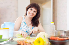 Positive  woman cutting the celery Royalty Free Stock Images