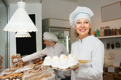 Positive woman display with pastery. Positive women with hats at confectionery display with pastry stock photo
