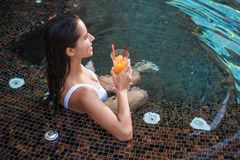 Positive woman drinking beverage in water stock photo