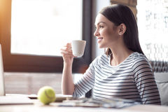 Positive woman drinking coffee. Open your mind. Pleasant cheerful smiling beautiful woman sitting at the table and expressing gladness while drinking coffee stock images