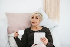 A positive woman drinks a morning coffee lying in bed and uses a tablet to watch videos, listen to music and chat with royalty free stock images