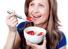 Positive woman eating cereals with strawberries Stock Photos