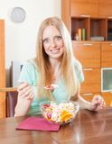 Positive  woman eating  fruit salad at home Stock Image