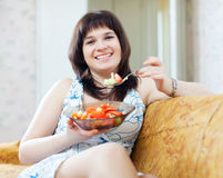 Positive  woman eats  tomatoes  salad Royalty Free Stock Images