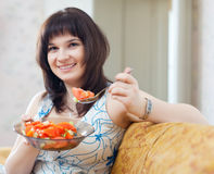 Positive  woman eats veggie salad on sofa Royalty Free Stock Image