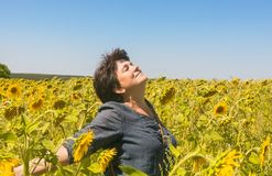 Positive woman among field of sunflowers Stock Photo
