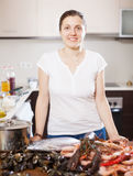 Positive woman with fresh raw sea food Stock Photo