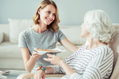 Positive woman giving her mother a tasty pie Royalty Free Stock Images