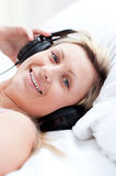 Positive woman with headphones on lying on her bed Stock Photo