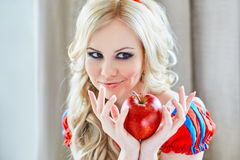 Positive woman holding an apple Stock Photo