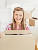 Positive woman holding a box in her new house Stock Photos