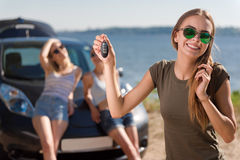 Positive woman holding keys from the car. Lets have a ride. Positive beautiful women holding keys from the car and smiling while her friends standing in the Royalty Free Stock Image