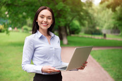 Positive woman holding laptop. Modern user. Positive smiling beautiful woman expressing gladness and using laptop while standing outdoor royalty free stock image