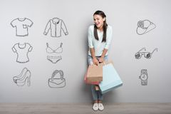 Positive woman holding paper bags after coming home from a shopping mall. Shopping time. Cheerful delighted young person holding colorful paper bags and feeling Royalty Free Stock Photography