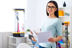 Positive woman holding papers. Ready to work. Cheerful smiling beautiful woman holding papers and expressing gladness while her colleague sitting in the Royalty Free Stock Photo