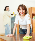 Positive woman with husband dusting wooden furiture Stock Photos