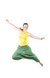 Positive Woman jumping. Happy beautiful woman in green Indian trousers jumping at white background Royalty Free Stock Photo