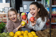 Positive woman and little girl posing whith apples in department Royalty Free Stock Images