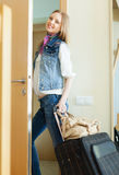 Positive woman with luggage leaving  home Stock Image