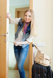 Positive woman with luggage loocking door Stock Image