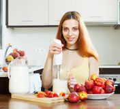 Positive woman making beverages with nectarines and milk Royalty Free Stock Images