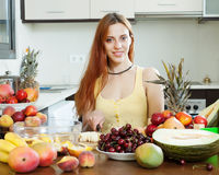 Positive  woman making  fruit salad Royalty Free Stock Image