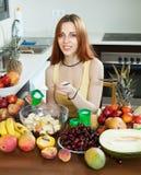 Positive   woman making  fruit salad with cream Stock Photos