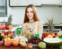 Positive woman making  fruit  salad with yoghourt. In home kitchen Stock Photo