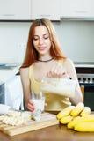 Positive  woman making milkshake with bananas Stock Image