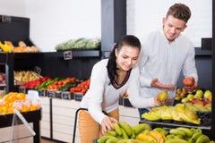 Positive woman and man choosing various fruits stock photos