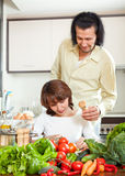 Positive woman and man salt to the pot and in home kitchen Stock Photography