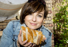 Positive woman offering fresh sliced bread. Young positive woman offering fresh sliced bread Royalty Free Stock Image