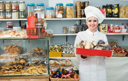 Positive woman offering fresh and tasty pastry Royalty Free Stock Images