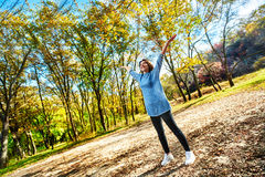 Positive woman in park. Positive young happy woman enjoying walk in autumn park Royalty Free Stock Photo