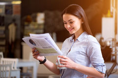 Positive woman reading newspaper. Informational whirlwind. Positive delighted beautiful woman drinking coffee and reading newspaper while expressing gladness royalty free stock photos