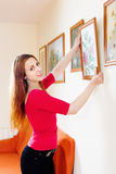 Positive  woman in red hanging the art pictures Stock Photos