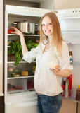 Positive woman searching for something in refrigerator Stock Photos