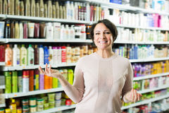 Positive woman selecting hair care products Royalty Free Stock Image