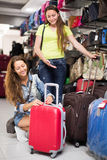 Positive woman selecting suitcase Royalty Free Stock Image