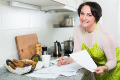 Positive woman signing financial papers in kitchen Stock Photos