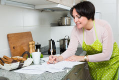 Positive woman signing financial papers in kitchen Royalty Free Stock Photos