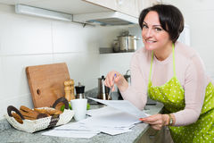 Positive woman signing financial papers in kitchen Royalty Free Stock Photo