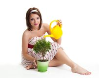 Positive woman sit and water plant Stock Photo