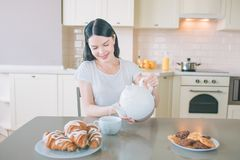 Positive woman sits at table in kitchen. She smiles and poures water into white cup. There are plates with cookies nad royalty free stock photos