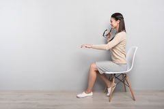 Positive woman sitting in the chair Stock Photography