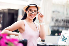 Positive woman sitting at the table. Express gladness. Cheerful delighted beautiful young woman sitting at the table and touching her glasses while resting in stock images