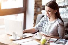 Positive woman sitting at the table. In touch with world. Pleasant delighted smiling beautiful woman sitting at the table and expressing gladness while using stock photos
