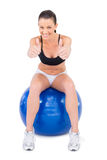 Positive woman in sportswear sitting on exercise ball giving thumbs up to camera Stock Images