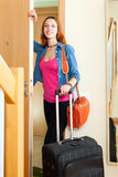Positive woman with suitcase near door at home Royalty Free Stock Photos
