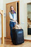 Positive woman with suitcase near door Stock Photography